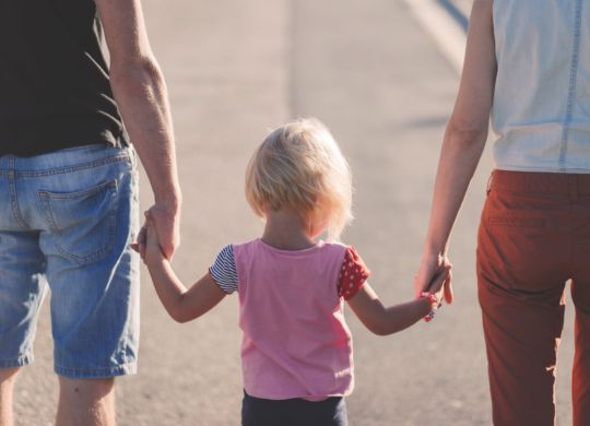 A girl holding her parents` hands.