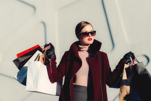 A girl with sunglasses shopping, with bags. Do your shopping in the best fashion cities in Europe.