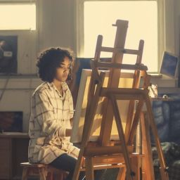 Woman sitting in front of a canvas and painting