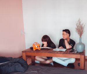 A couple sitting on the floor. She is reading and he is looking at a weird looking pig statue