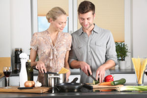 A couple making a dish in a fancy kitchen