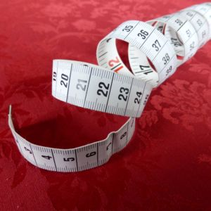 A measuring tape on a red surface.