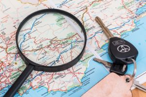 car keys and magnifying glass on a map