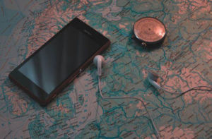 A smartphone and earphones next to a compass, on a map of Scandinavia.