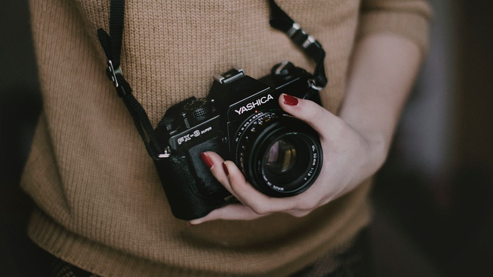 A girl holding a digital camera.