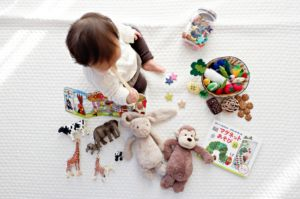 A child surrounded by toys.