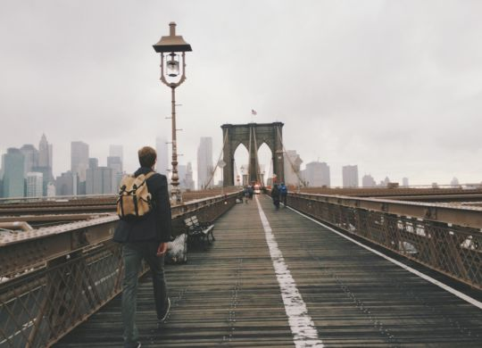 A person walking on a NYC bridge.