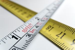 Two measuring tapes are showing feet and meters.