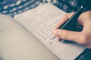 A hand writing down a checklist.
