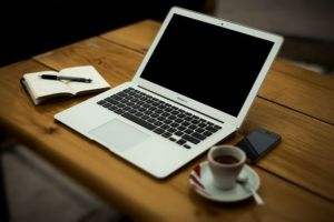 A cup of coffee, notebook, pen, laptop and mobile phone on a table.
