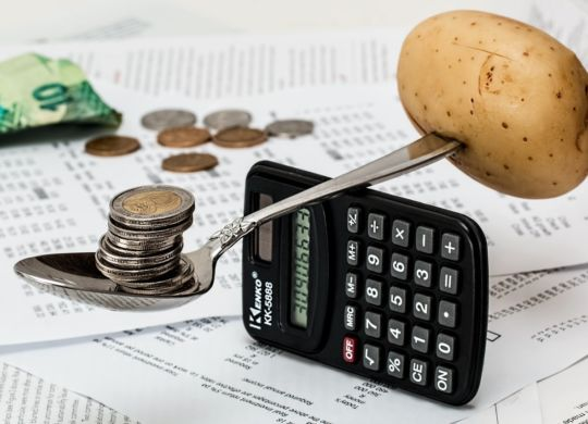 A spoon ona calculator, a pile of coins on its one side and a potato on the other.