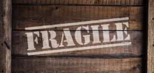 Fragile written in large white letters on a wooden box.