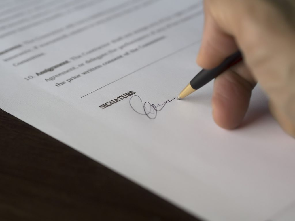 A person siging a document.