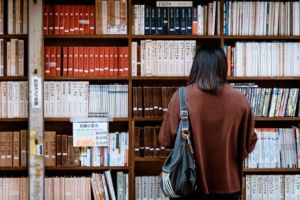 There is a woman with a bag, standing in front of some bookshelves.