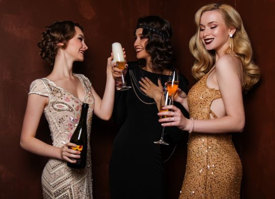 Women drinking champagne after reading New York City nightlife guide