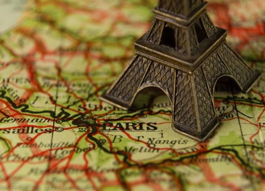 a small Eiffel Tower on a map of France