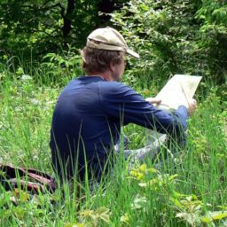A man sitting on a gradd and reading an Ontario guide for Europeans