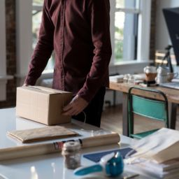 A guy in a burgundy shirt packing something in a cardboard box.