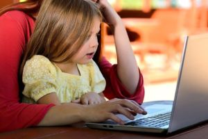 A mother and daughter looking at a laptop studying the information about helping your child adjust to a new culture.