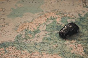 A map of a part of Europe with a small toy car representing traveling.