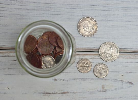 Some coins in and next to a jar.