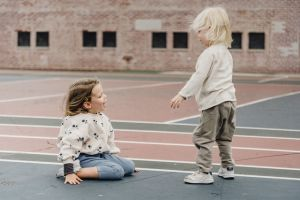 Two kids are playing on the playground.