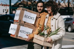 A man is holding some moving boxes, and a woman is holding a box with some plants.