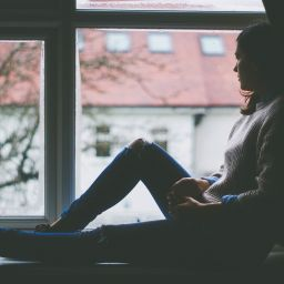 A young girl sitting by the window and thinking about the challenges Europens face after moving to NYC.