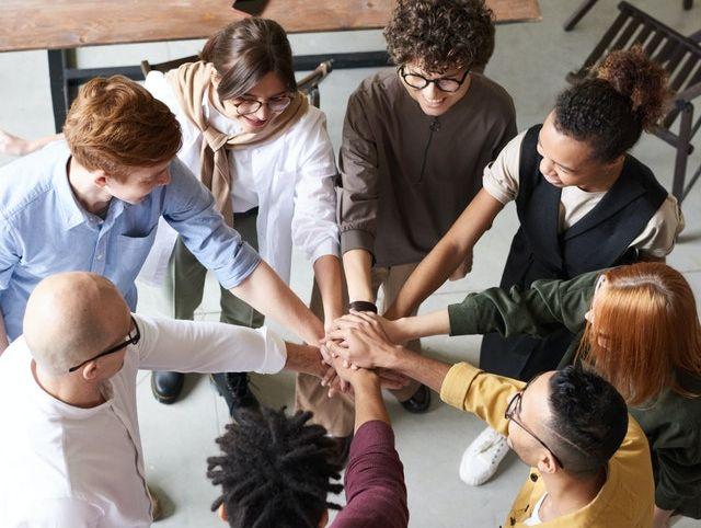 Smiling employees making team handshake.