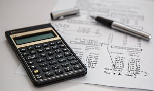 A financial paper and a calculator to define the budget when buying a house in NY state.
