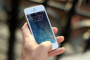 A man holding an Iphone.