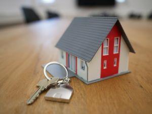 A house-shaped keyring and a house key.
