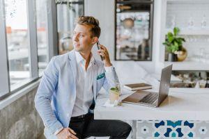 a man near white desk talking on a phone